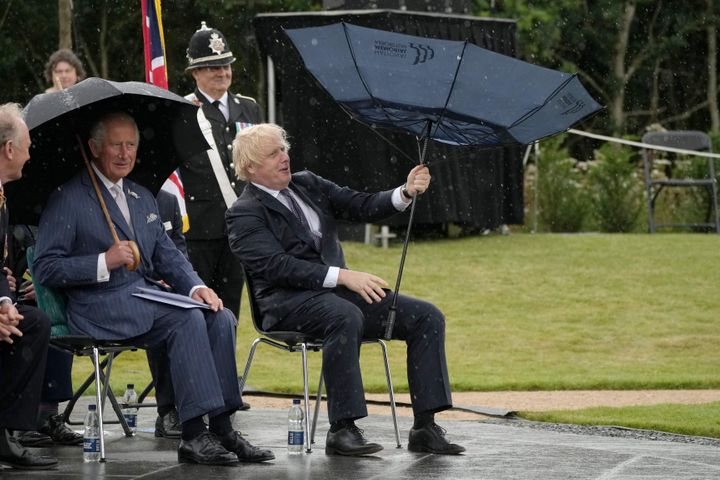 British Prime Minister Boris Johnson tries to open his umbrella next to Prince Charles at the dedication ceremony of the new
