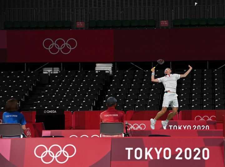 Viktor Axelsen of Denmark competes in a near-empty stadium during a men's singles badminton match during the Tokyo Olympics on July 24, 2021.