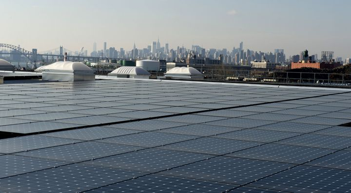 The New York City skyline unfolds behind solar panels atop a restaurant in the northernmost borough of The Bronx.