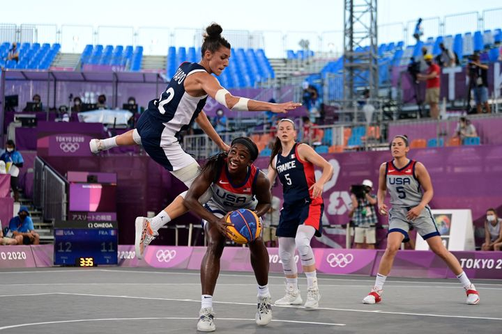 With almost no audience to cheer them on, France's Laetitia Guapo, left, fights for the ball with Team USA's Jacquelyn Young, center, during the women's semifinal 3x3 basketball match on July 28, 2021.