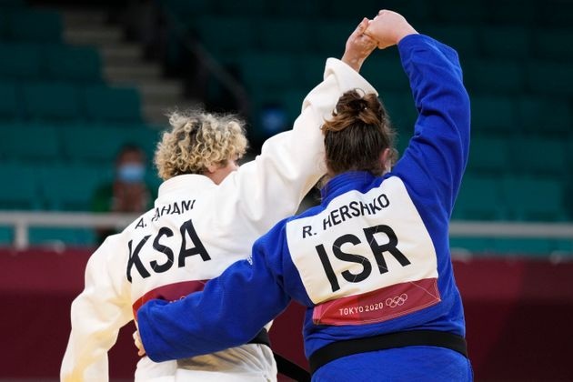 Tahani Alqahtani of Saudi Arabia, left, and Raz Hershko of Israel react after competing in their women's...