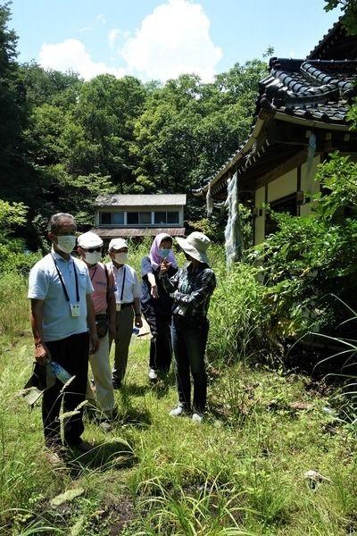 三瓶さんの自宅前で語り合う原告団の住民ら=2021年7月19日、福島県浪江町津島