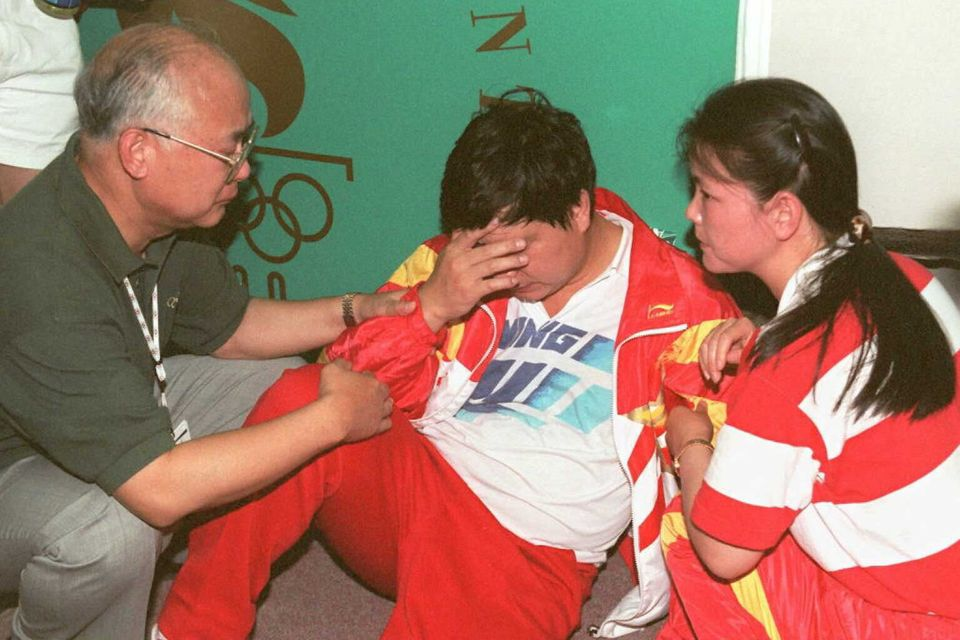 ATLANTA, GA - JULY 20: China's Wang Yifu is attended by Chinese team officials after he collapsed during...