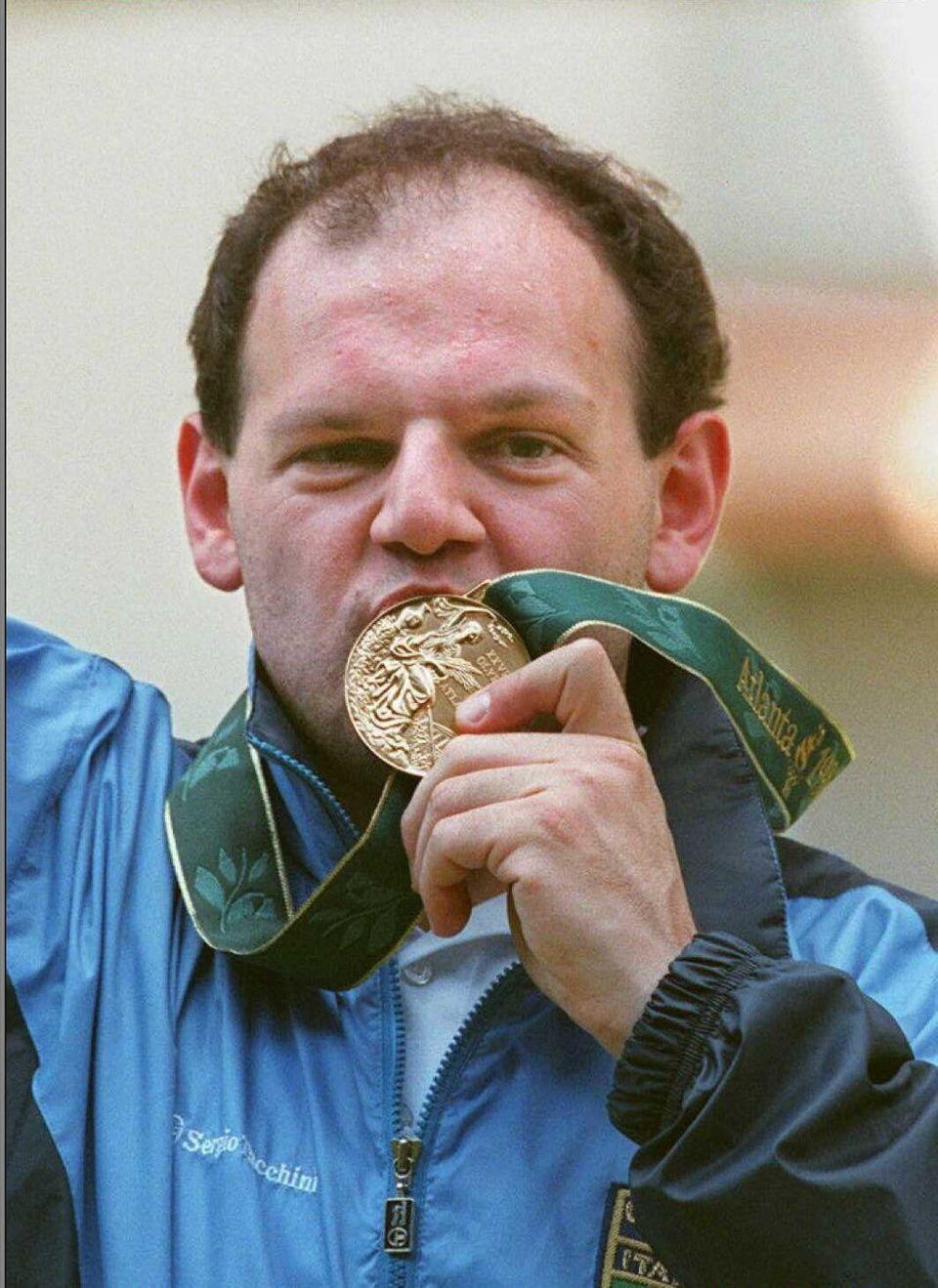 ATLANTA, GA - JULY 20: Italy's Roberto Di Donna bites his gold medal after winning the men's air pistol...