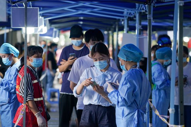 A medical worker registers information of residents at a nucleic acid testing spot in Nanjing, capital...
