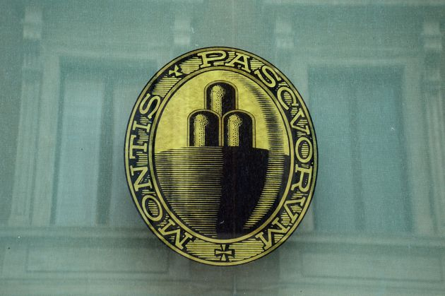 The logo of the Monte dei Paschi di Siena bank is seen on the window of a branch in downtown Rome on...