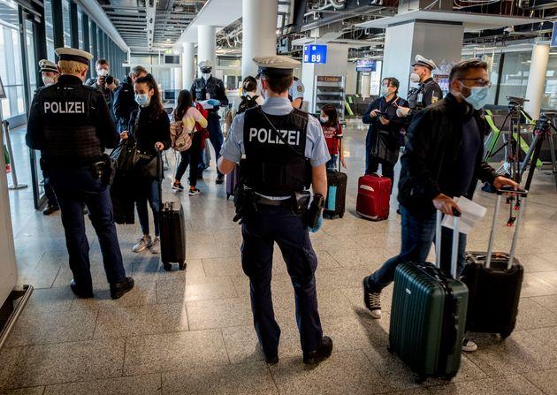 Γερμανοί αστυνομικοί ελέγχουν για αρνητικά τεστ κορονοϊού επιβάτες που φτάνουν στο αεροδρόμιο της Φρανκφούρτης από τη Μαγιόρκα (AP Photo/Michael Probst, File)