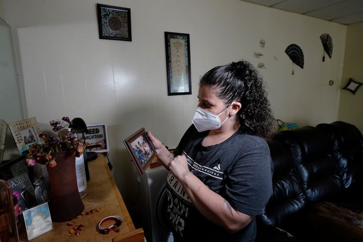 Roxanne Schaefer holds a photograph in the living room of her apartment, in West Warwick, R.I., Tuesday, July 27, 2021.