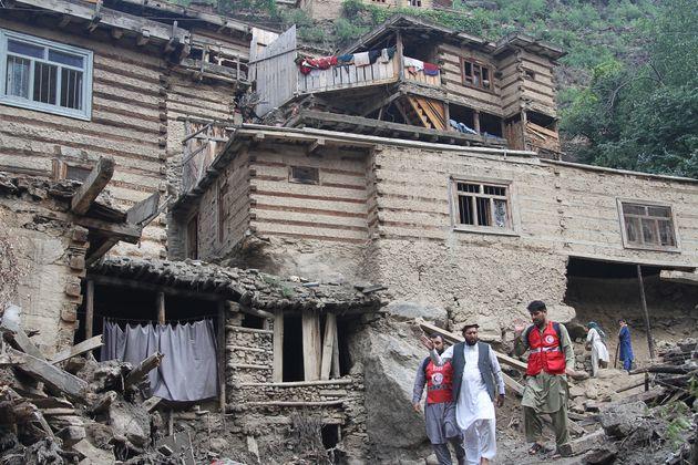 Des personnes face à des habitations endommagées suite aux crues dans la province du Nuristan province,...