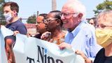 Minnesota Attorney General Keith Ellison (center left) and Sen. Bernie Sanders (center right) march to the polls with congressional candidate Nina Turner (center) on Saturday.