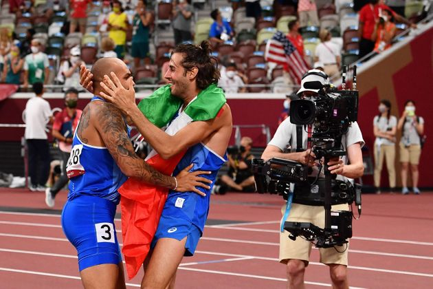 Italy's Lamont Marcell Jacobs celebrates with high jumper Italy's Gianmarco Tamberi after winning the...