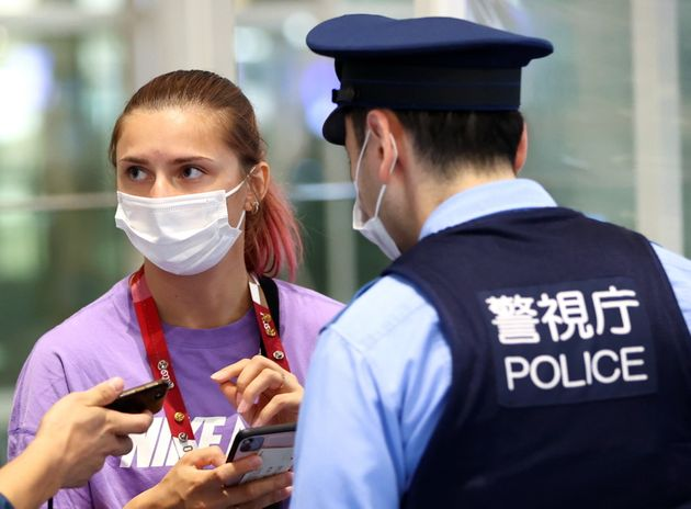 H Λευκορωσίδα σπρίντερ Krystsina Tsimanouskaya συνομιλεί με αστυνομικό στο διεθνές αεροδρόμιο Χανέντα του Τόκιο, 1/8 2021. REUTERS/Issei Kato