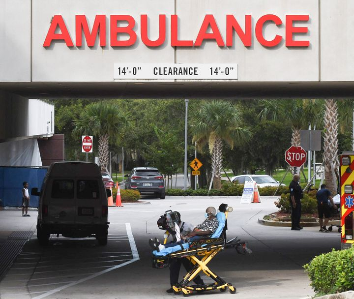 A patient is brought on a gurney to the emergency department at AdventHealth hospital in Orlando on July 26, the day that hos