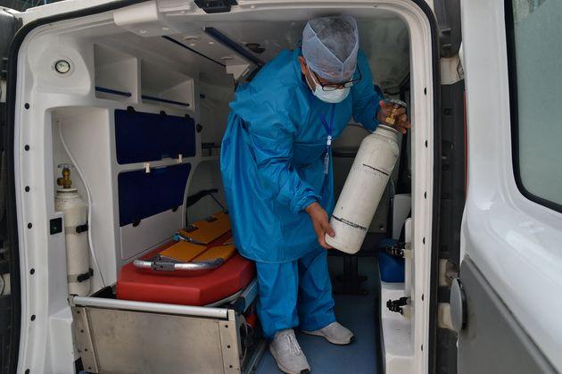 Un soignant algérien porte une bouteille d'oxygène à Blida, en Algérie, le 28 juillet