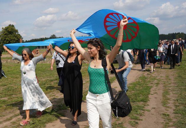 Un grupo de mujeres levantan banderas gitanas en Auschwitz-Birkenau, durante un homenaje a las víctimas...