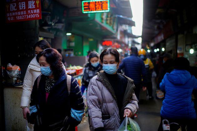 Des passants dans un marché de Wuhan, le 8 février