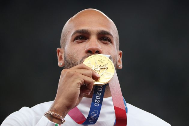 TOKYO, JAPAN - AUGUST 02: Gold medalist Lamont Marcell Jacobs of Team Italy kisses his gold medal on...