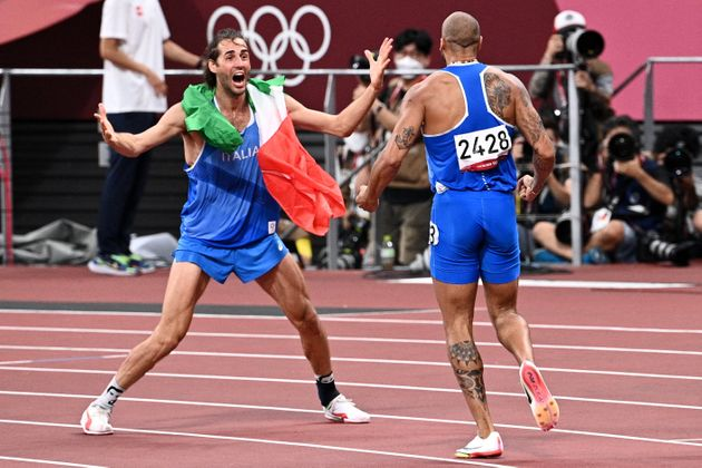 Italy's Lamont Marcell Jacobs (R) celebrates with high jumper Italy's Gianmarco Tamberi after winning...