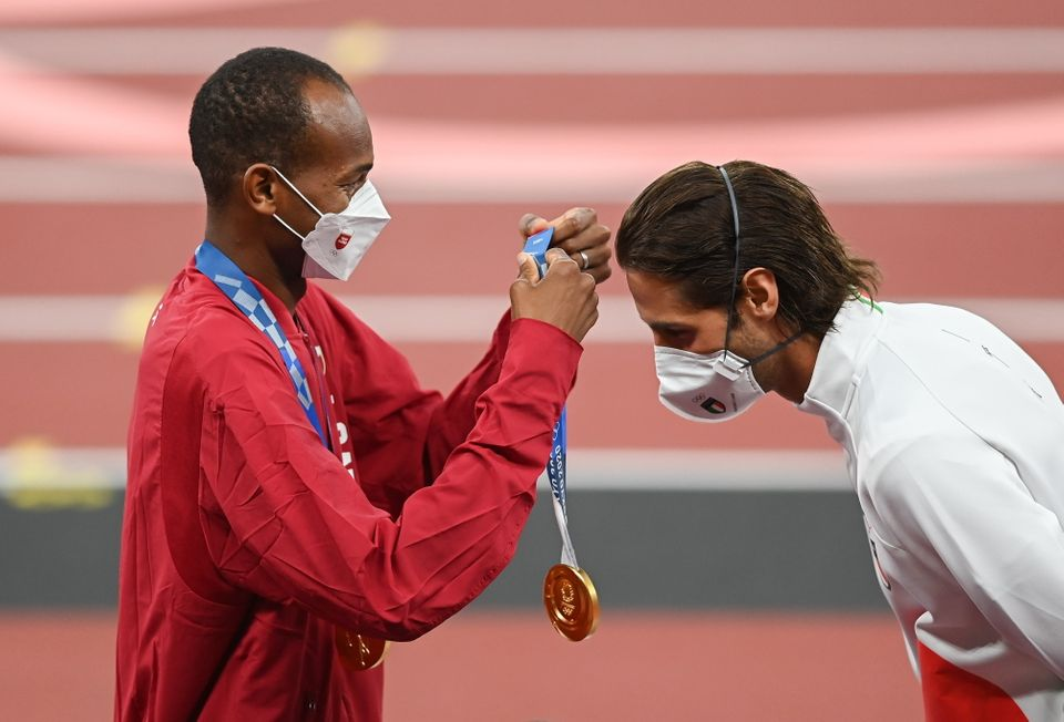Gold medalist Mutaz Essa Barshim of Qatar, left, presents Gianmarco Tamberi of Italy with his gold medal...