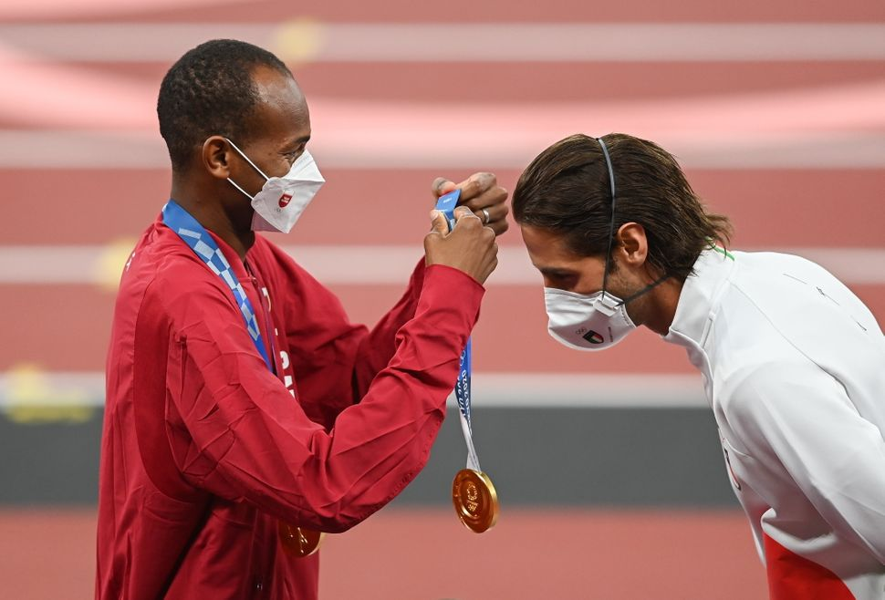 Gold medalist Mutaz Essa Barshim of Qatar, left, presents Gianmarco Tamberi of Italy with his gold medal during the men's hig