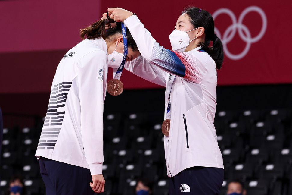 Bronze medalists Kim Soyeong, left, and Kong Heeyong of Team South Korea place their medals on each other during the ceremony