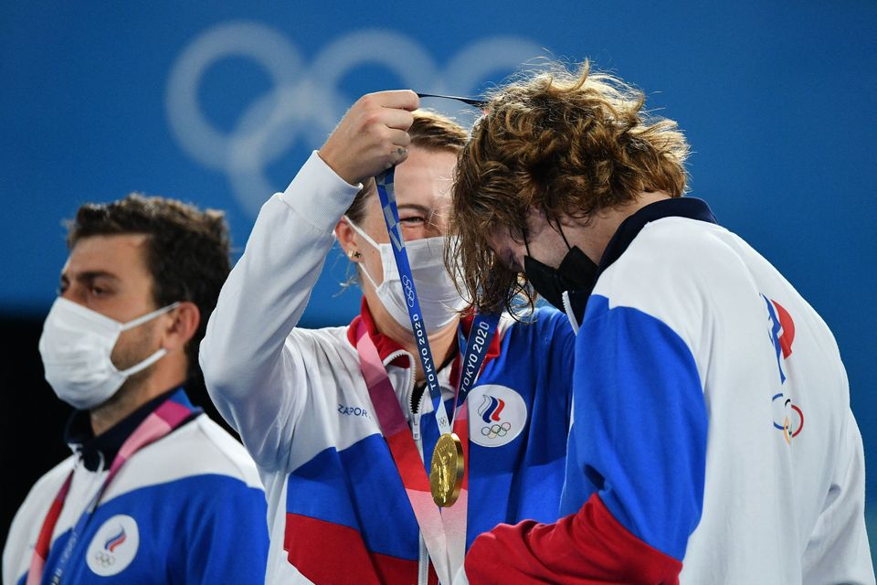 Gold medalists Anastasia Pavlyuchenkova, center, and Andrey Rublev, right, of the Russian Olympic Committee...