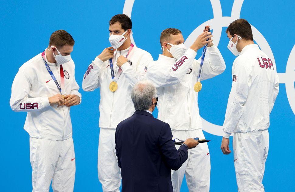 The USA's Caeleb Dressel, second from right, helps teammate Zach Apple on the podium. Dressel, Apple, Ryan Murphy (far left)