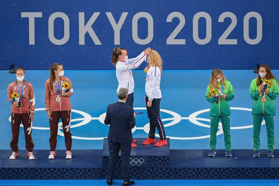 The Czech Republic's Barbora Krejcikova, center, places a medal on teammate Katerina Siniakova. The pair won gold in women's
