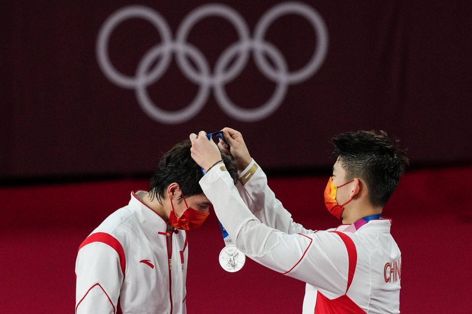 Silver medalists Li Junhui and Liu Yuchen of Team China are seen during the medal ceremony for the men's doubles badminton ev