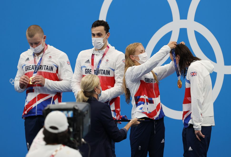 Anna Hopkin presents Kathleen Dawson of Team Great Britain with her medal during the ceremony for the mixed 4 x 100 meter med