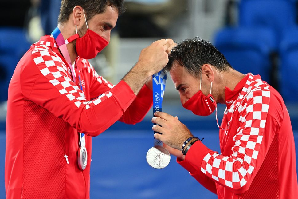 Silver medallist Marin Cilic of Croatia, left, gives Croatia's Ivan Dodig his silver medal on the podium during the men's dou