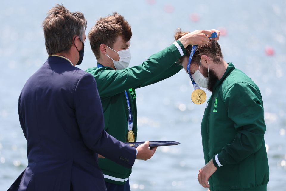 Ireland's Fintan McCarthy places a gold medal on teammate Paul O'Donovan at the medal ceremony for men's...