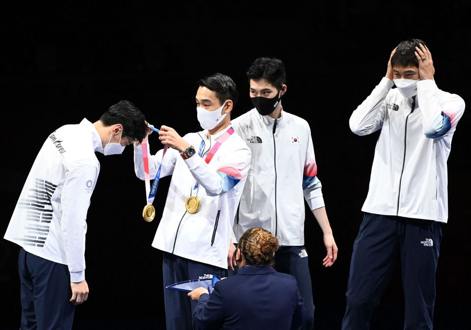 South Korea fencers receive their gold medals on the podium during the medal ceremony for the men's sabre...