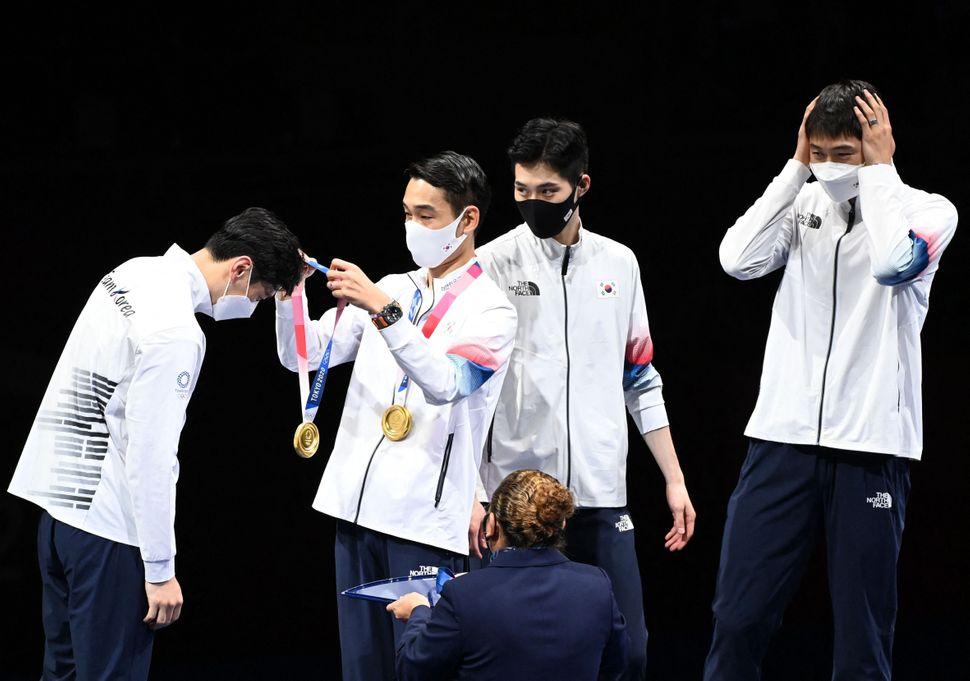 South Korea fencers receive their gold medals on the podium during the medal ceremony for the men's sabre team on July 28.