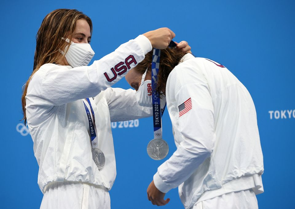 Katie McLaughlin of Team United States places a silver medal around the neck of her teammate Katie Ledecky...