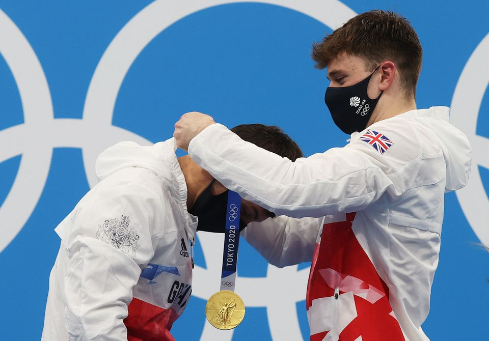 Great Britain's Tom Daley receives a gold medal from teammate Matty Lee during the medal presentation...