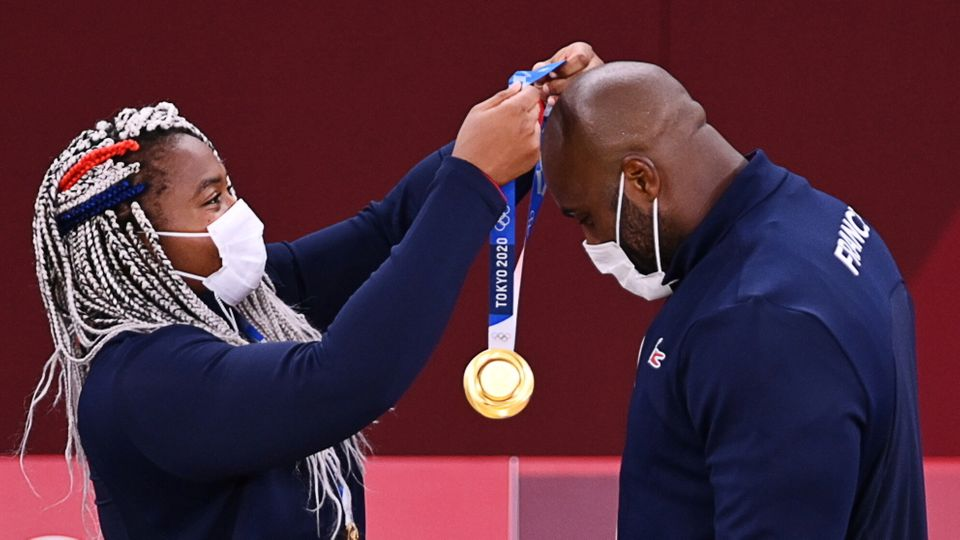 Gold medalist Teddy Riner of France, right, receives a medal from teammate Romane Dicko. France won gold...