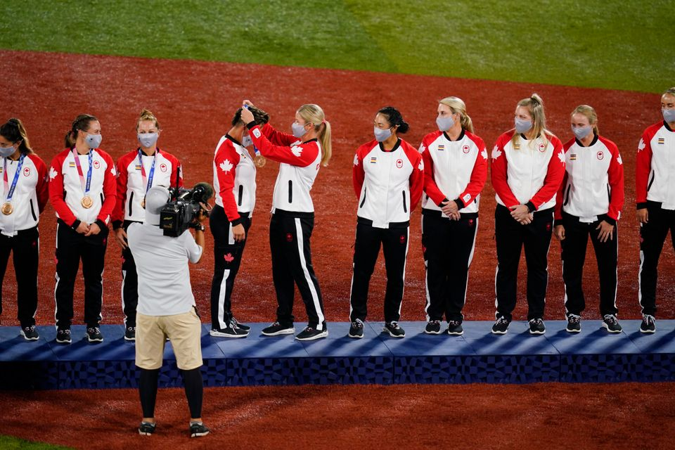 Members of Team Canada receive their bronze medals on the podium during the medal ceremony for softball...
