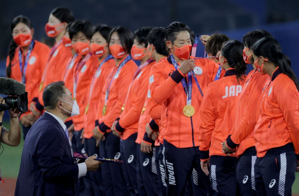 Softball player Yukiko Ueno of Japan (fourth from right) puts the gold medal on catcher Haruka Agatsuma (third from right) on