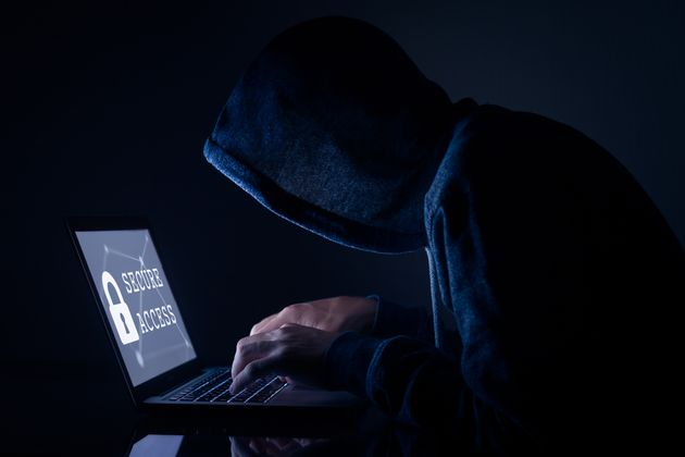 Hooded hacker in dark room performing a cyber attack to a secure access to steal data on internet, laptop...