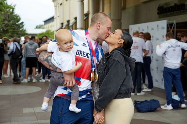 Adam Peaty kisses his wife Eirianedd Munro whilst holding their son George-Anderson Peaty at Heathrow...