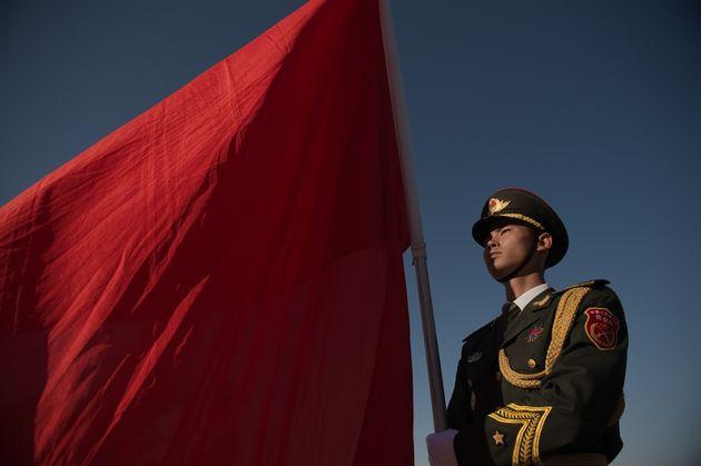 Un membre de la garde d'honneur militaire chinoise tient un drapeau rouge à l'occasion d'une cérémonie...