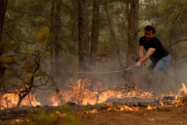 A man tries to extinguish a fire near the Cardak neighbourhood of Manavgat district of Antalya,