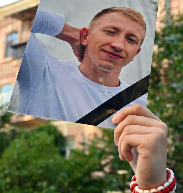 A picture of Vitaly Shishov is held by an activist as he takes part in a rally outside the Belarus embassy in Kiev on August