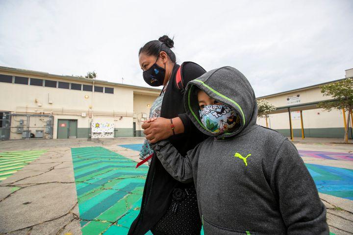 First grade student Daniel Cano, 5, and his mom, Sonia Cano, walk past COVID-19 safety precaution signs at Euclid Avenue Elem