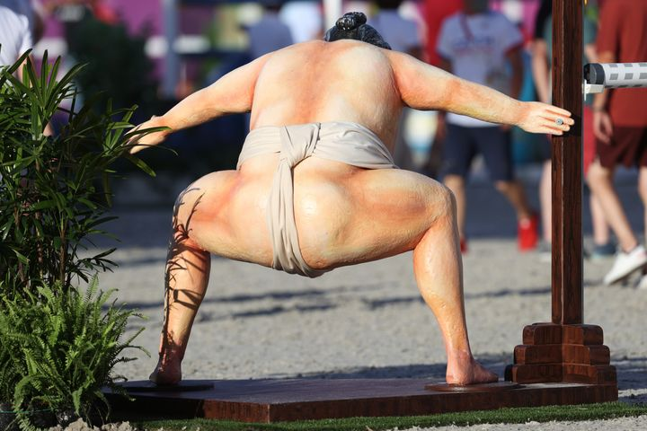 A rear view of the sumo wrestler during the equestrian jumping.