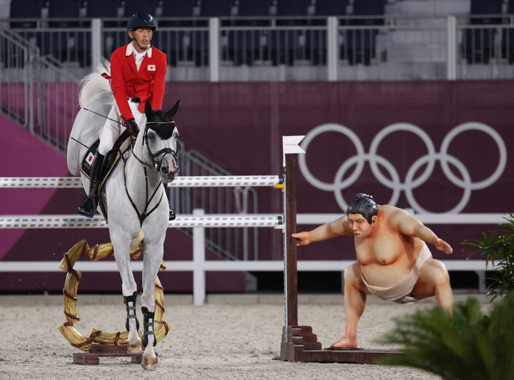 A rider clears the barrier as the statue of a sumo wrestler looks in the Tokyo Olympics equestrian competition. )