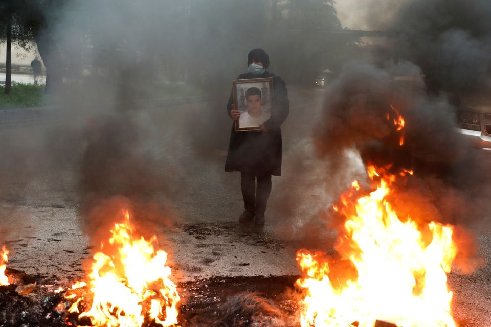 A woman holds a picture of one of the blast's victims during a protest earlier this