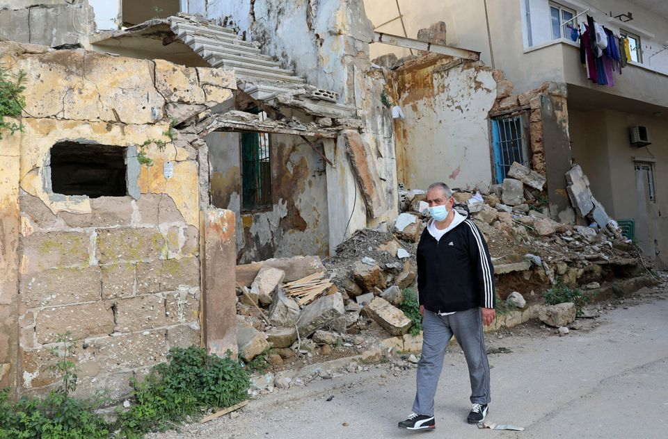 Local resident outside buildings damaged by the