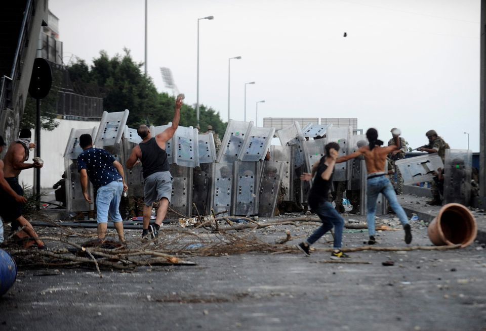 Protestors throw stones at Lebanese army members in Beirut in July this year as demonstrations